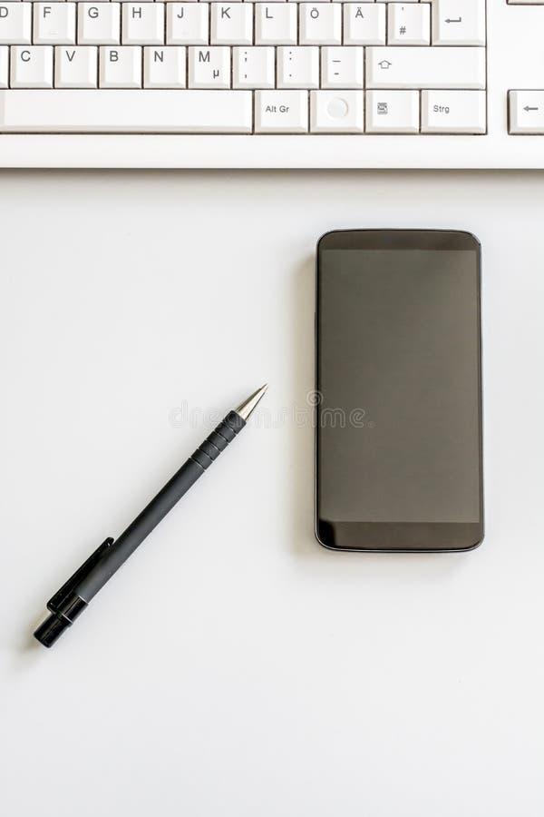 Mesa arrumada com o teclado do smartphone, da pena e de computador fotografado de cima de fotos de stock