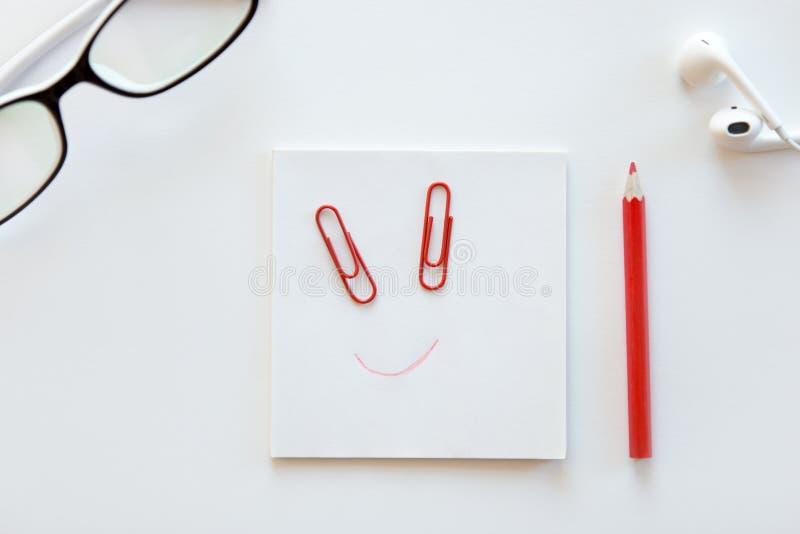 Mesa branca com bloco de papel, um sorriso tirado nele foto de stock