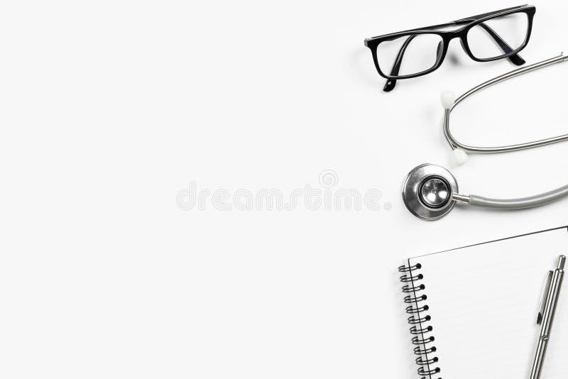 Mesa branca do doutor com o caderno do estetoscópio com vidros da pena e do olho Vista superior com espa?o da c?pia, configura??o imagens de stock royalty free