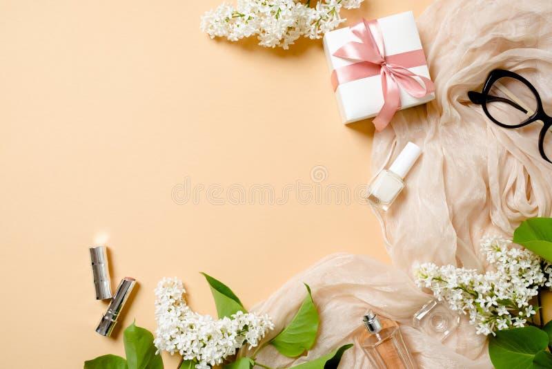 Mesa colocada lisa das mulheres com lenço de seda, caixa de presente, vidros, flores lilás, cometárias no fundo da cor pastel Esc fotografia de stock