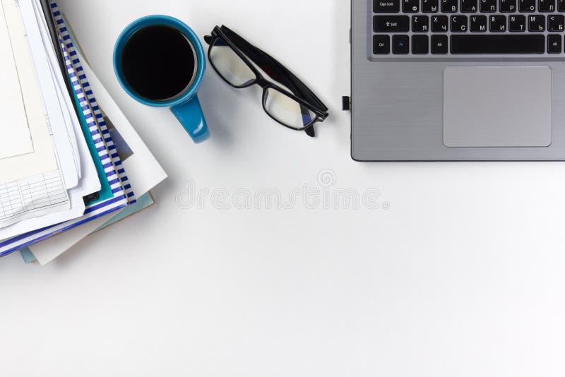 A mesa com fontes, almofada da tabela do escritório de nota vazia, copo, pena, PC, amarrotou o papel, flor no fundo branco Vista  fotos de stock