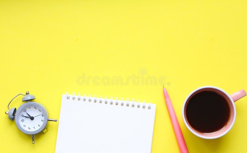 Mesa com fontes, caderno do estudante, copo de caf?, pena, mini despertador no fundo amarelo fotografia de stock royalty free