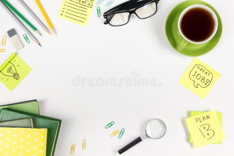 A mesa com fontes do verde, almofada da tabela do escritório de nota vazia, copo, pena, vidros, amarrotou o papel, lupa, flor sob fotografia de stock royalty free