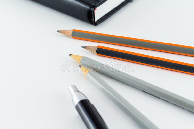 Mesa com a pena e o lápis do diário da agenda imagem de stock