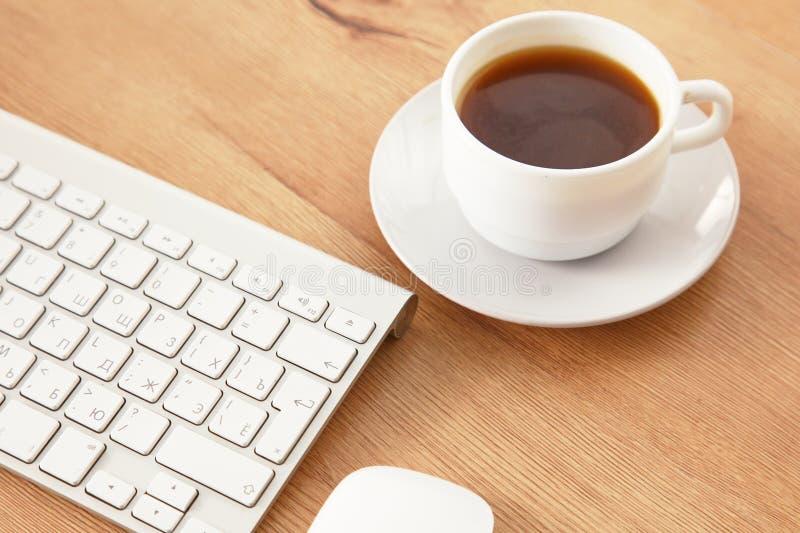 Mesa com portátil, vidros do olho, fone de ouvido, pena e uma xícara de café imagem de stock