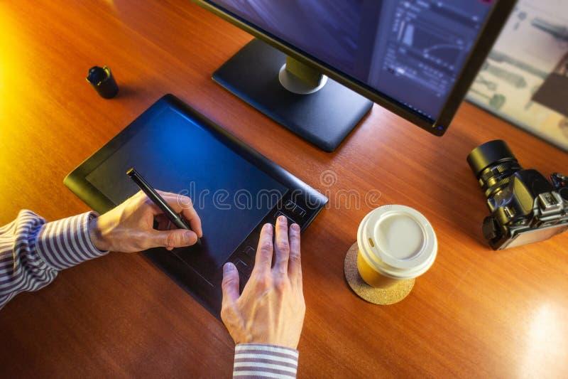 Mesa con el ordenador, la tableta de gráficos y una taza de café foto de archivo libre de regalías