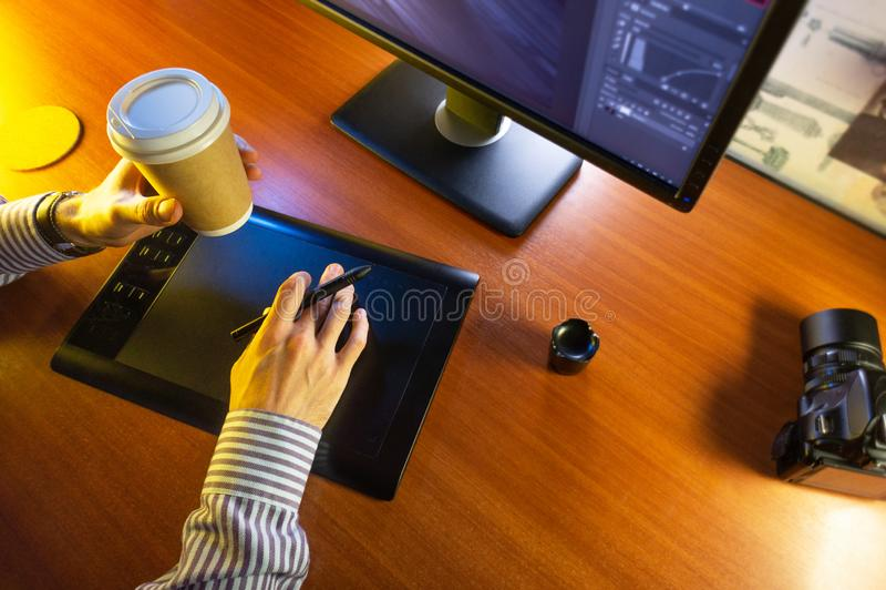 Mesa con el ordenador, la tableta de gráficos y una taza de café fotografía de archivo