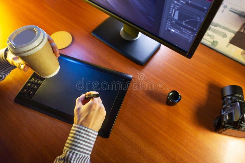 Mesa con el ordenador, la tableta de gráficos y una taza de café fotos de archivo