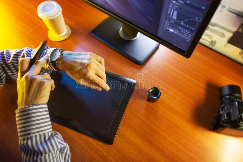 Mesa con el ordenador, la tableta de gráficos y una taza de café imagen de archivo