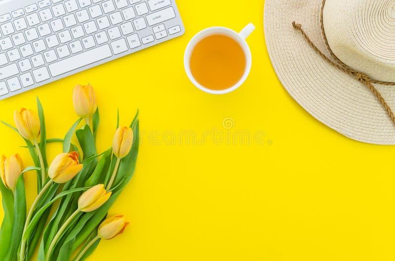 Mesa con los tulipanes amarillos, el sombrero de paja, la taza de té y el teclado blanco del ordenador con el espacio de la copia imagen de archivo libre de regalías