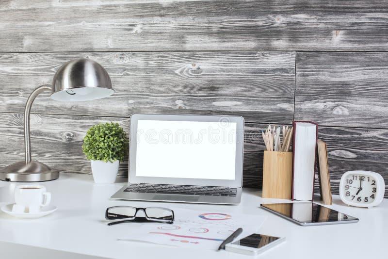 Mesa creativa de la oficina con el ordenador portátil blanco en blanco fotos de archivo libres de regalías