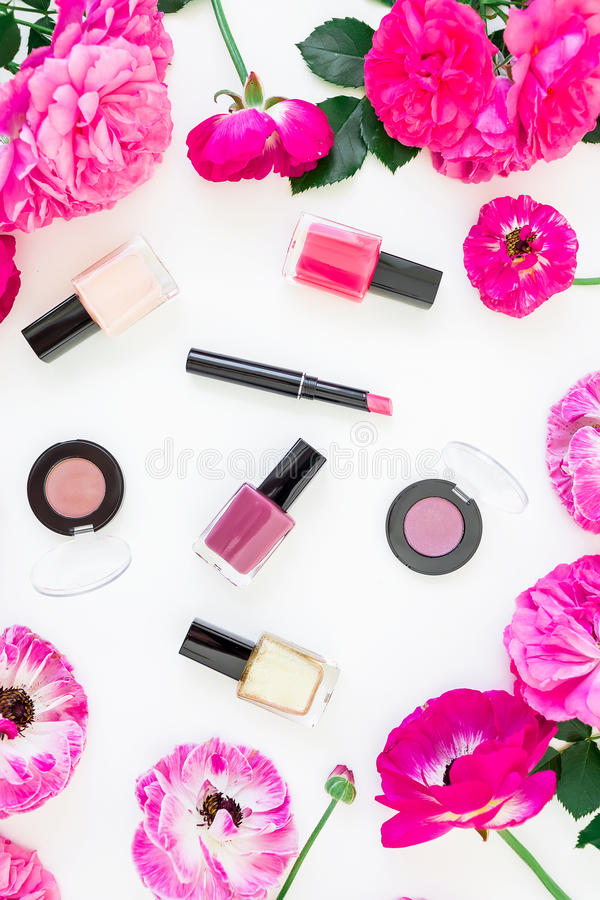 Mesa da beleza com cosméticos, batom, sombras para os olhos, verniz para as unhas e quadro de flores cor-de-rosa no fundo branco  fotografia de stock