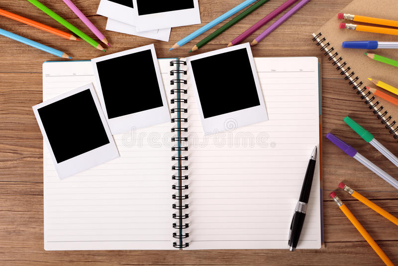 Mesa da estudante universitário com álbum de fotografias vazio e diversas cópias do polaroid fotos de stock royalty free