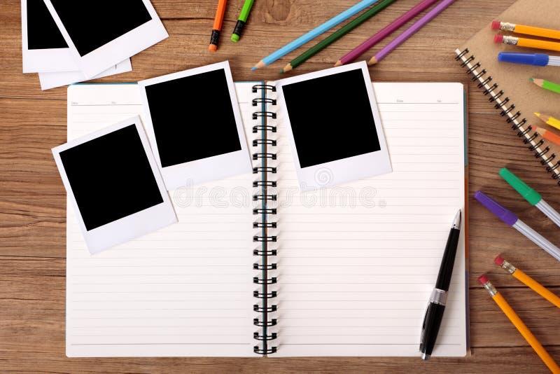 A mesa da estudante universitário com álbum de fotografias vazio e diverso foto do polaroid imprime imagem de stock royalty free