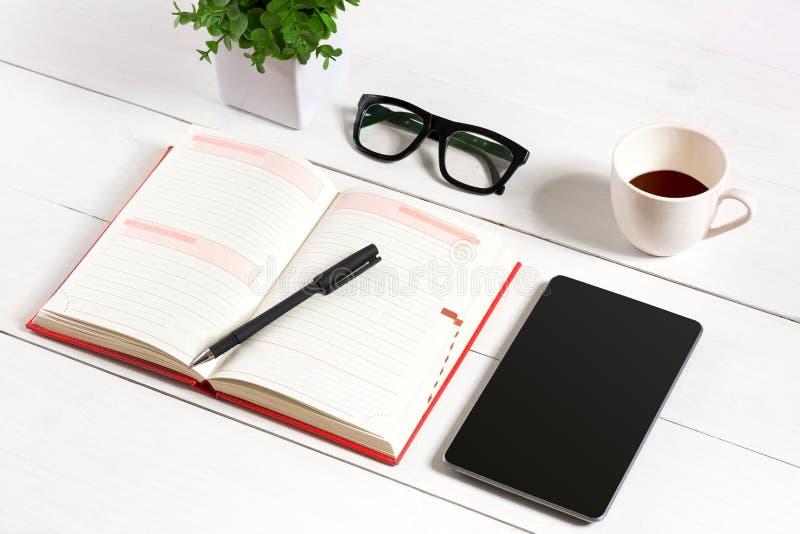 Mesa da tabela do escritório com grupo de fontes, bloco de notas vazio branco, copo, pena, tabuleta, vidros, flor no fundo branco fotografia de stock royalty free