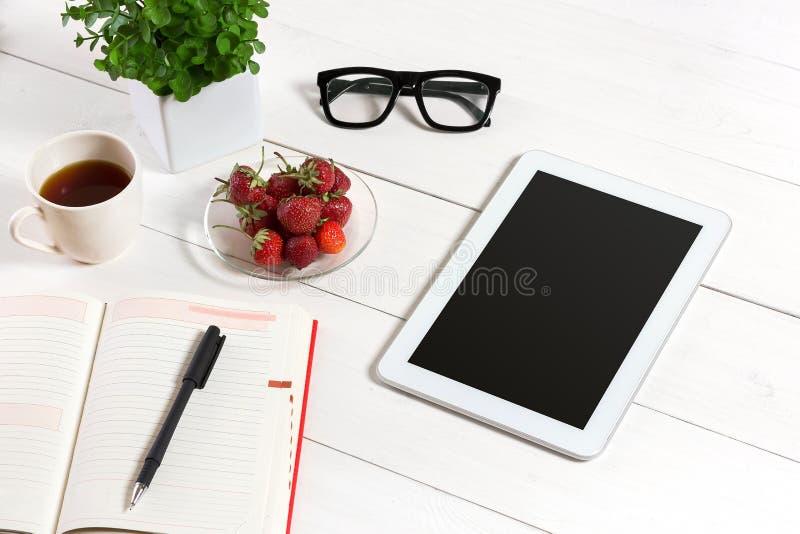 Mesa da tabela do escritório com grupo de fontes, bloco de notas vazio branco, copo, pena, tabuleta, vidros, flor no fundo branco foto de stock