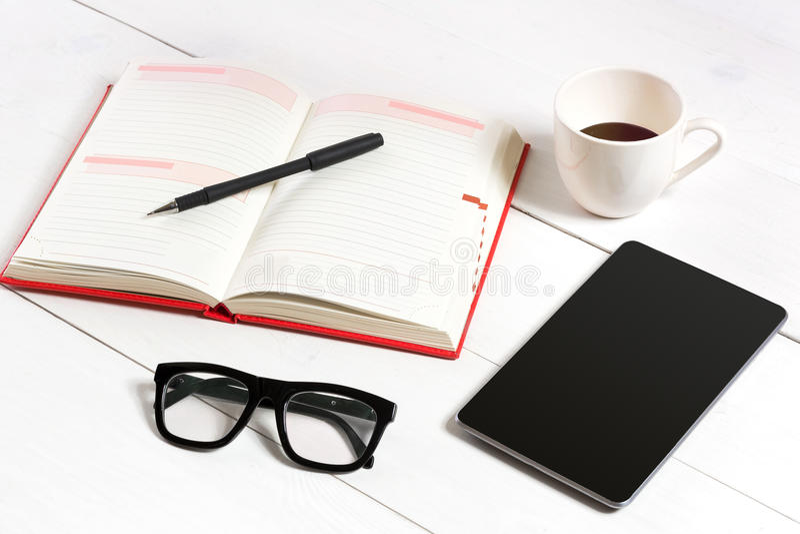 Mesa da tabela do escritório com grupo de fontes, bloco de notas vazio branco, copo, pena, tabuleta, vidros no fundo branco Vista imagem de stock royalty free