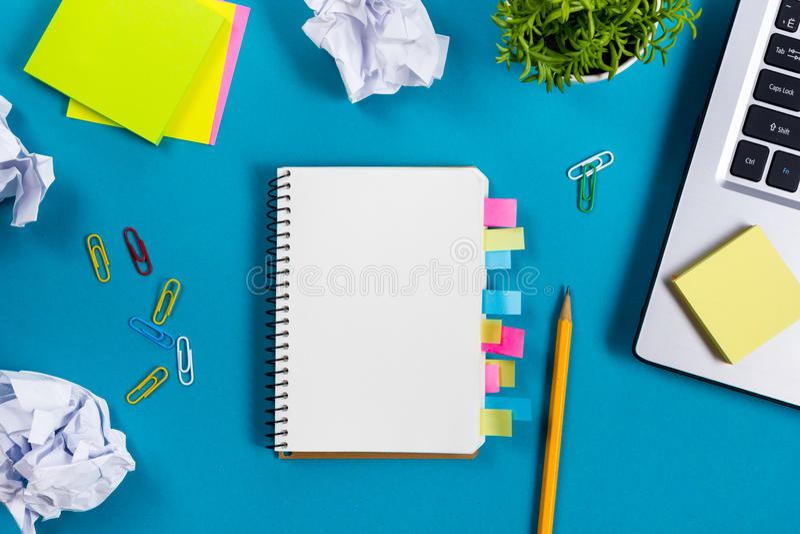 A mesa da tabela do escritório com grupo de fontes coloridas, almofada de nota vazia branca, copo, pena, PC, amarrotou o papel, f imagens de stock