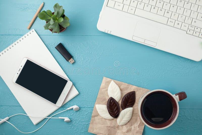 Mesa da tabela do escritório Espaço de trabalho com diário, planta, fones de ouvido, café, lápis na tabela azul Vista superior, c foto de stock