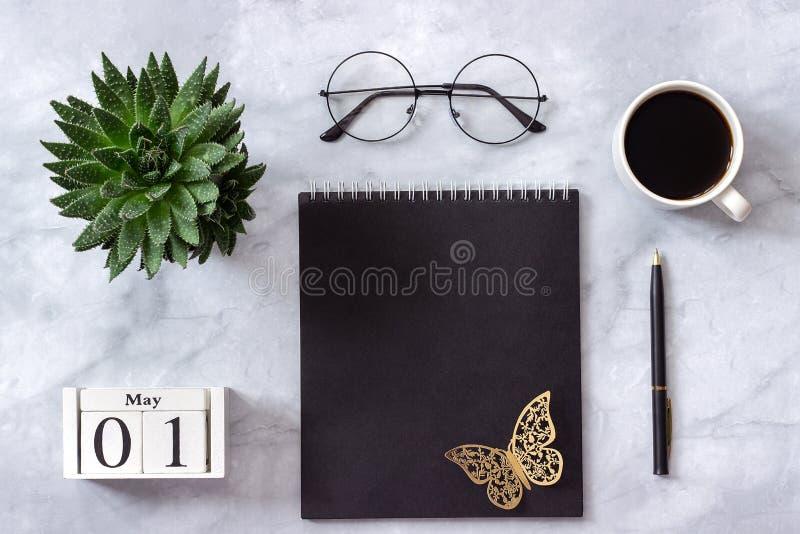Mesa da tabela do escritório ou da casa Cubos calendário bloco de notas de madeira do preto do 1º de maio, xícara de café, planta imagens de stock royalty free