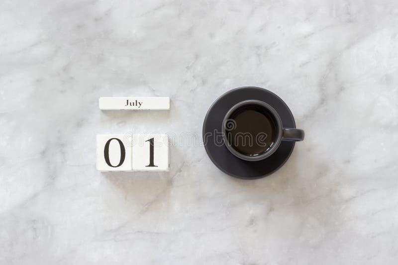 Mesa da tabela do escrit?rio ou da casa Cubos calendário o 1º de julho e xícara de café de madeira no plano à moda do local de tr imagem de stock royalty free