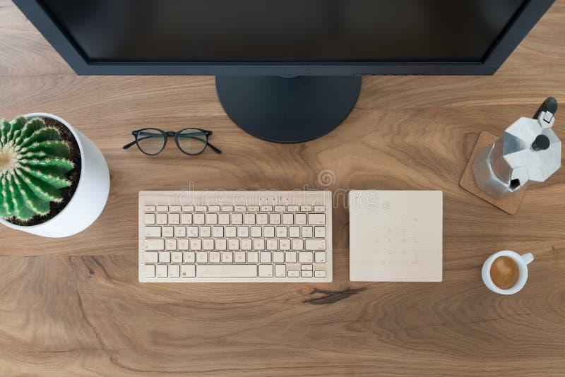 Mesa da tabela do escrit?rio da vista superior Espaço de trabalho com a grande tela de monitor, um teclado de madeira, um trackpa fotografia de stock royalty free