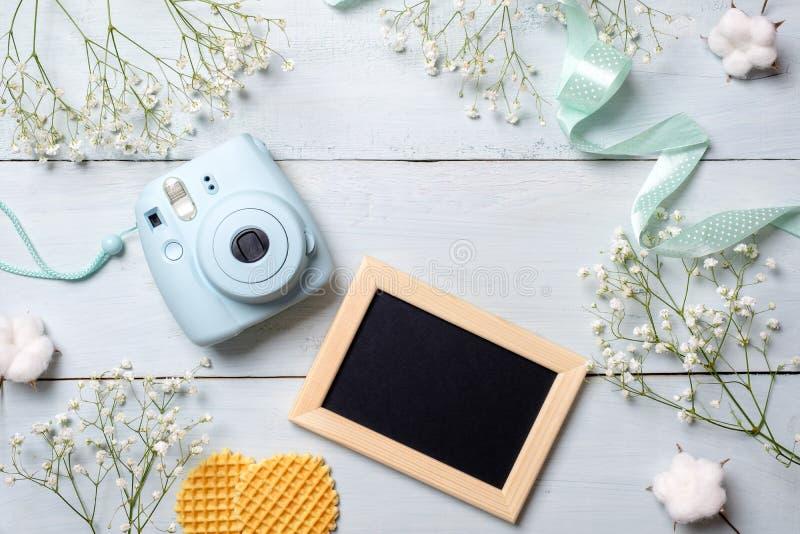 A mesa das mulheres com câmera da foto, moldura para retrato, cookies Quadro mínimo das flores da mola, cores pastel, estilo colo foto de stock