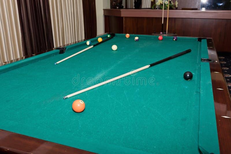 Mesa de bilhar gasta com uma sugestão e bolas no grande salão do gu imagem de stock royalty free