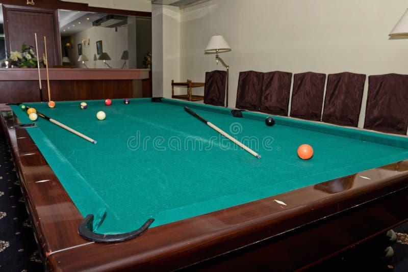 Mesa de bilhar gasta com uma sugestão e bolas no grande salão do gu imagem de stock