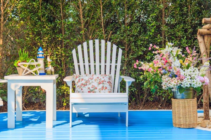 Mesa de centro y silla con las flores en el jardín fotos de archivo