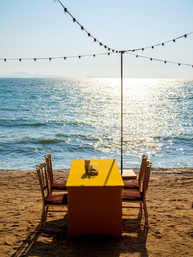 Mesa de comedor con cuatro sillas en la playa foto de archivo