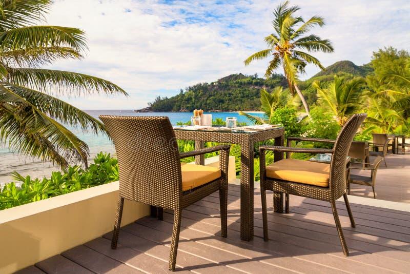 Mesa de comedor con las sillas en decking de madera, por el mar, isla de Mahe, Seychelles fotos de archivo