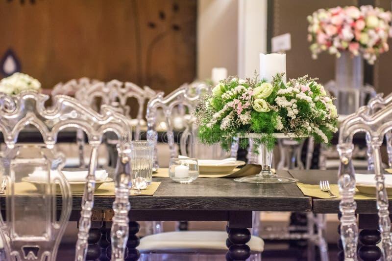 Mesa de comedor de lujo con las sillas y la flor foto de archivo