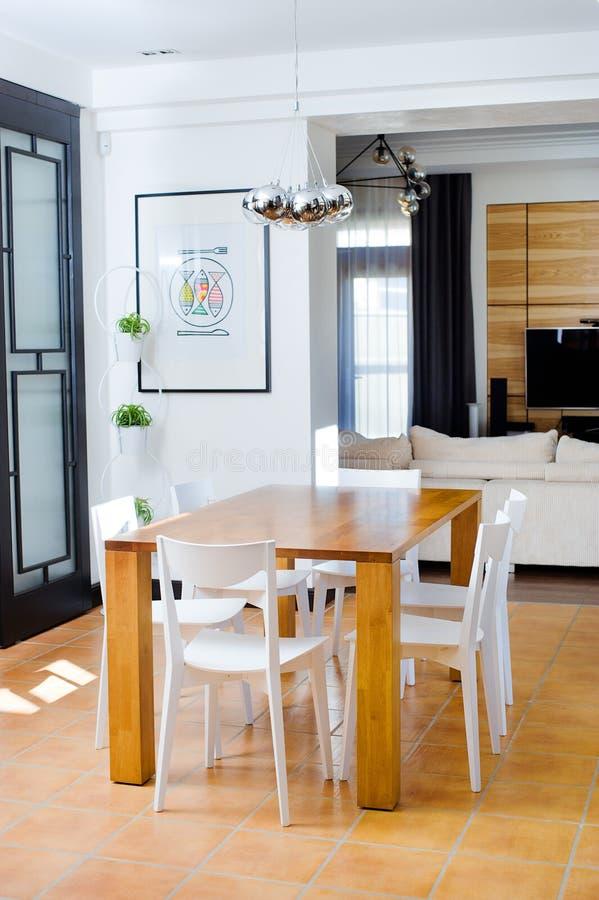 Mesa de comedor de madera con las sillas blancas imagen de for Sillas de comedor blancas de madera