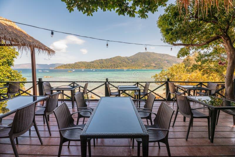 Mesa de comedor en terraza con la opini?n tropical hermosa del mar fotografía de archivo