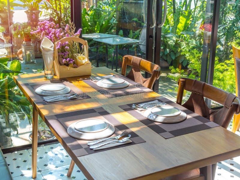 Mesa de comedor fijada en restaurante con sol romántica imagenes de archivo