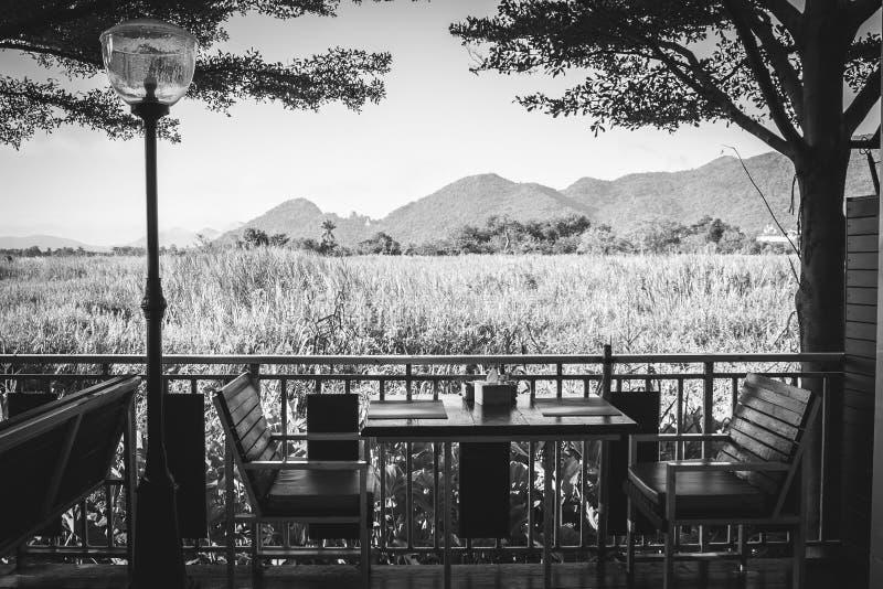 Mesa de comedor de madera y silla de la imagen blanco y negro abstracta en restaurante con el fondo natural hermoso de la visión fotos de archivo libres de regalías