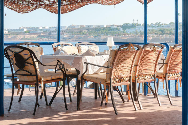 Mesa de comedor maravillosamente fijada del restaurante que pasa por alto el mar imagenes de archivo