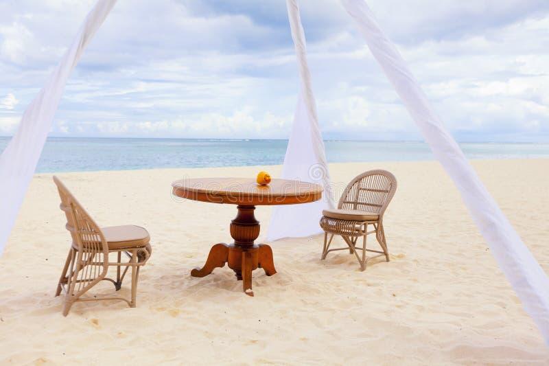 Mesa de comedor privada y sillas de mimbre para la cena romántica para los pares de la luna de miel en una playa tropical imagen de archivo libre de regalías