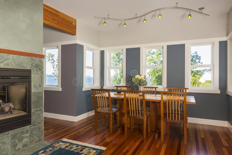 Mesa de comedor y sillas con los pisos de madera, las paredes pintadas, la iluminación del acento y las ventanas de la visión en  fotos de archivo libres de regalías