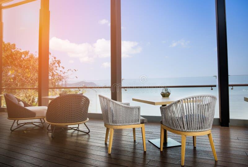 Mesa de comedor y sillas en el tarrace con la opinión de la playa imagen de archivo libre de regalías