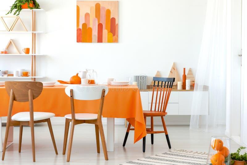 Mesa de cozinha coberta com a toalha de mesa alaranjada e os pratos brancos Arte finala na parede e prateleira no canto imagem de stock royalty free