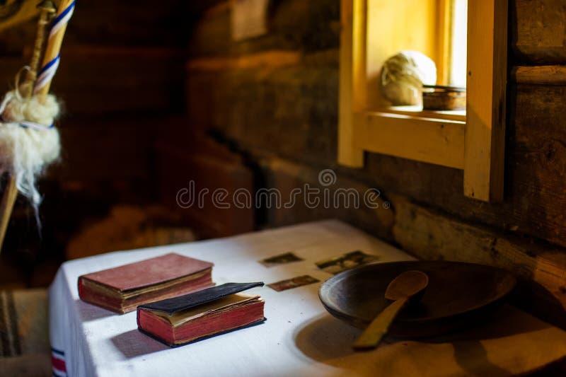 Mesa de cozinha de madeira do vintage rural com livros e utensílios de cozimento ao redor foto de stock