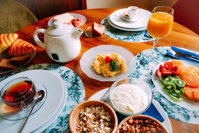 Mesa de desayuno con la variedad de comidas incluyendo los cereales, el yogur, los huevos revueltos, la fruta, el cruasán y bebid imagen de archivo libre de regalías