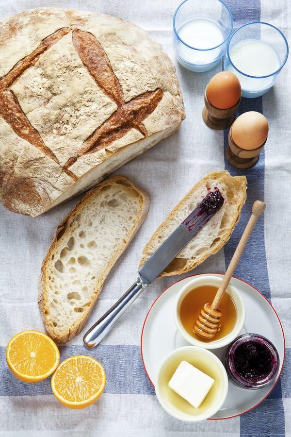 Mesa de desayuno Empane e hirvió los huevos, la mantequilla y la miel con la mermelada, fotografía de archivo