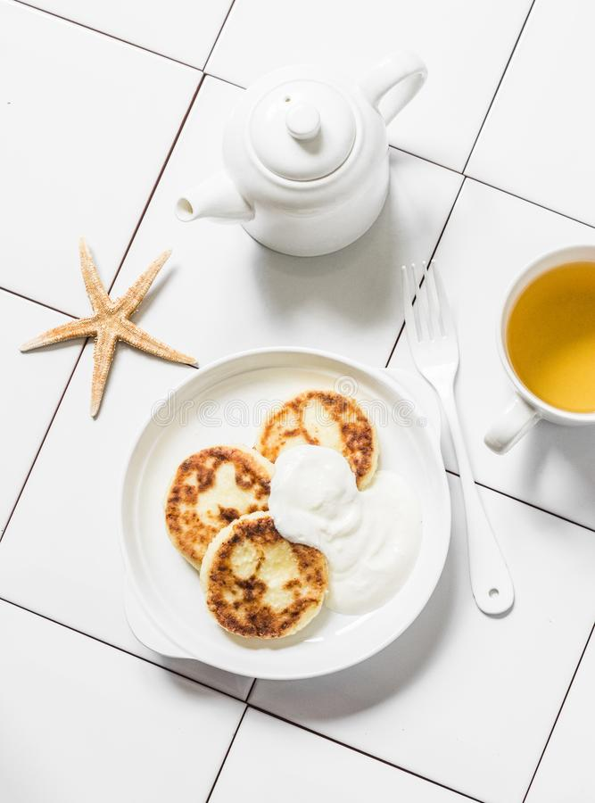 Mesa de desayuno de la mañana - crepes del té verde y del requesón en un fondo ligero, visión superior foto de archivo libre de regalías