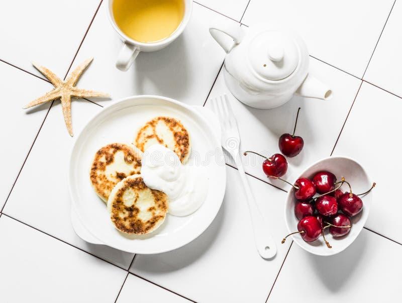Mesa de desayuno de la mañana - té verde, cereza y crepes del requesón en un fondo ligero, visión superior foto de archivo