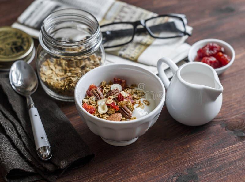 Mesa de desayuno de la mañana - yogur griego con el granola hecho en casa en un fondo oscuro fotografía de archivo