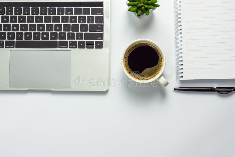 Mesa de escritório com copo de café, o caderno vazio, o potenciômetro preto da pena, do laptop e do cacto fotografia de stock