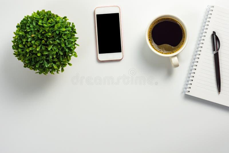 Mesa de escritório com a tela vazia, o copo de café, o potenciômetro da planta, o caderno e a pena pretos imagens de stock
